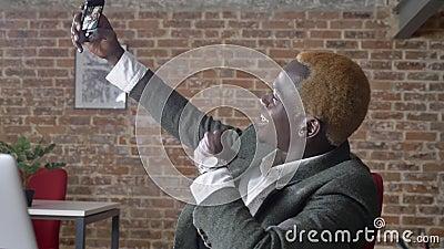 Jonge modieuze Afrikaanse Amerikaanse zakenman die selfie en in modern bureau zitten, zeker en succesvol nemen stock video