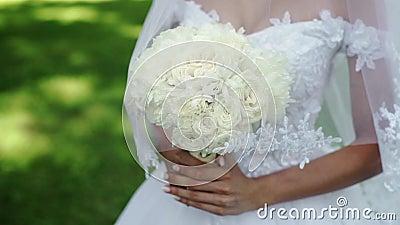 Jonge mooie bruid in huwelijks witte kleding met boeket van witte rozen die in een park bij de zomerdag blijven stock footage