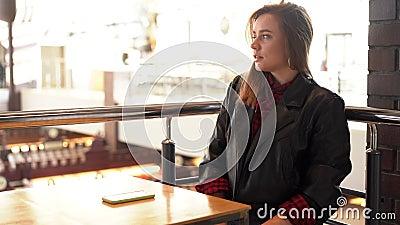 Jonge, mooie caucasiaanse meid die in een café zit te kijken naar het telefoonscherm krijgt slecht nieuws en is boos stock footage