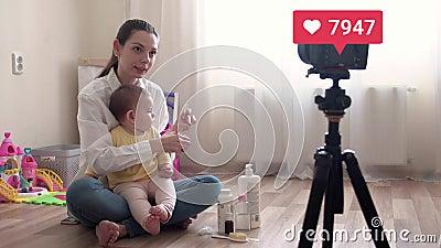 Jonge mooie moeder met babyopnamen, die vlog opneemt of live stream doet, en die een virel gaat met een geliefde teller 4.000 stock videobeelden