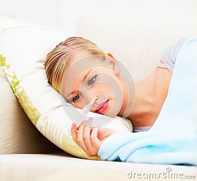 Jonge onwel vrouw die haar lichaamstemperatuur controleert