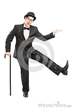 Jonge uitvoerder die in zwart kostuum een riet en het dansen houden