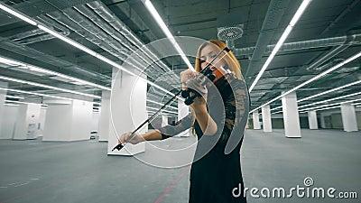 Jonge violist staat in een kantoorruimte en treedt op met een instrument stock footage