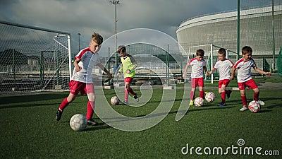 Jonge voetballers trein met ballen stock footage