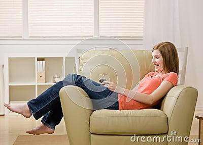 Jonge vrouw die aan mp3 speler op leunstoel luistert