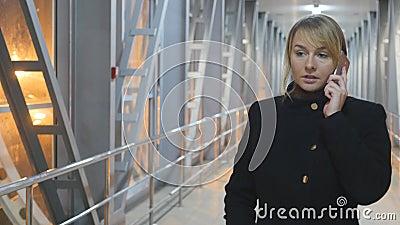 Jonge vrouw die op de telefoon en de gang in de nacht spreken binnen Portret van het aantrekkelijke meisje spreken op cellphone s stock videobeelden