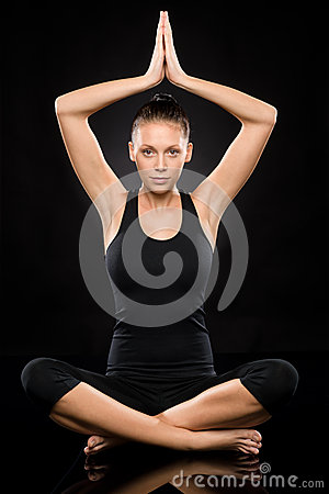 Jonge vrouw die yoga met opgeheven handen uitvoeren