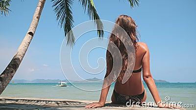 Jonge vrouw ontspant zich op het strand van het filippijnse paradijs stock footage