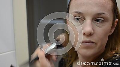 Jonge vrouw past poeder op haar gezicht toe met een borstel bij de spiegel stock video