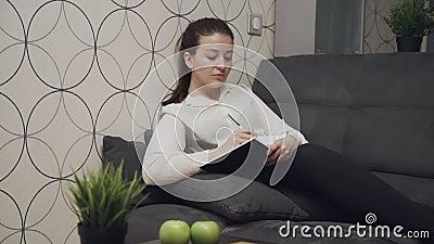 Jonge vrouw schrijft notities over het dagboek en ligt thuis op de bank tiener stock videobeelden