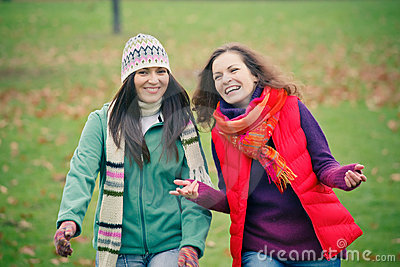 Jonge vrouw twee die in de herfstpark loopt
