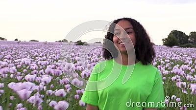 Jonge vrouw van meisjes die door het veld loopt van roze papaverbloemen stock footage