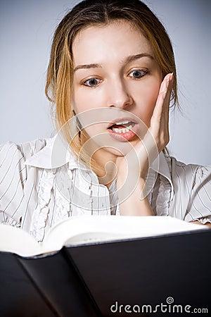 Jonge vrouw wordt verbaasd die door wat zij leest