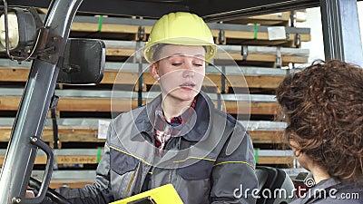 Jonge vrouwelijke fatory arbeiders werkende vorkheftruck bij de opslag die aan haar collega spreken stock video