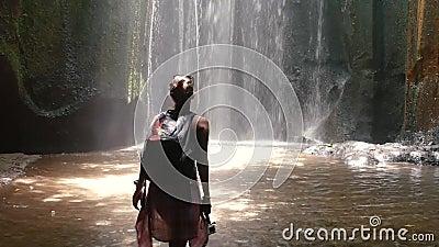 Jonge vrouwen open wapens aan verbazende waterval in Bali stock videobeelden
