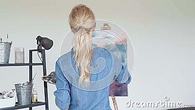 Jonge vrouwenkunstenaar die thuis creatieve het schilderen achtermening schilderen stock videobeelden