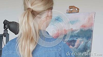 Jonge vrouwenkunstenaar die thuis creatieve het schilderen achtermening schilderen stock video