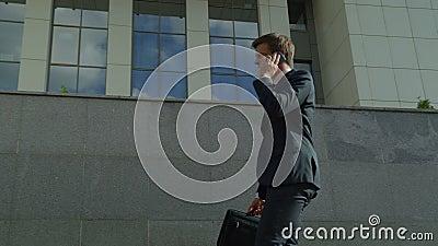 Jonge zakenman die op telefoon spreken, die vergadering beleggen, succesvol en zeker stock videobeelden