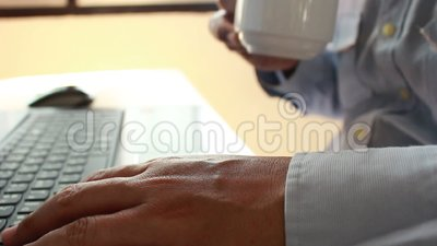 Jonge zakenman het drinken koffie en het gebruiken van laptop voor het bedrijfswerk in vage nadruk stock videobeelden