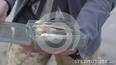 Jonge zekere visser die uitrustingsdoos bij het spinnen de visserij toont stock videobeelden