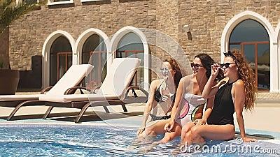 Jonge zonnige modellen met zwemkleding in de buurt van hotelzwembad stock videobeelden