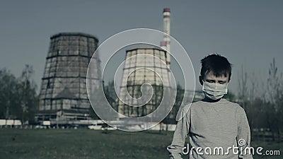 Jongelui die de koppelingen van het Verontreinigingsmasker zijn dragen hoofd en spijt Kerel die tegen Fabrieksschoorstenen blijve stock videobeelden