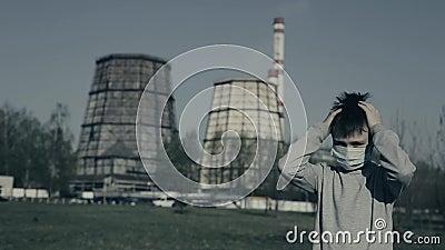 Jongelui die de koppelingen van het Verontreinigingsmasker zijn dragen hoofd en spijt Kerel die tegen Fabrieksschoorstenen blijve stock video