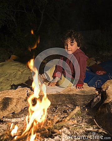 Jongen bij kampvuur