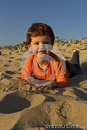 Jongen die op zijn buik op strand liggen