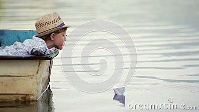Jongen die rieten hoedenzitting in de boot dragen die zijn document boot op een reis plaatsen stock videobeelden