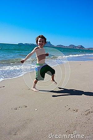 Jongen die rond op het strand springt