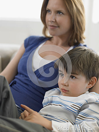 Jongen en Moeder die op TV thuis letten