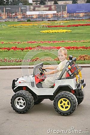 Jongen in stuk speelgoed auto