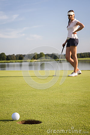 Joueur de golf de fille mettant sur le vert.