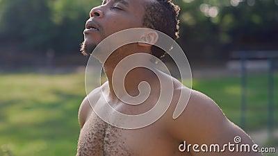 Jovem africano forte respirando profundamente no parque verde video estoque