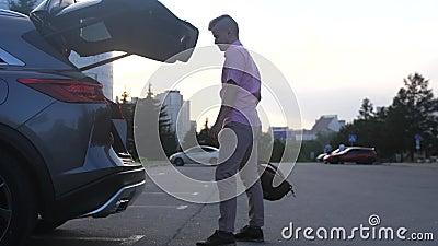 Jovem bonito abre o porta-malas, põe a mochila e fecha Sistema automático que abre o tronco por perna movimento lento filme