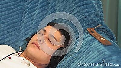 Jovem bronzeado se aproximando de uma camiseta branca em casa ouvindo música relaxante relaxamento, calma video estoque