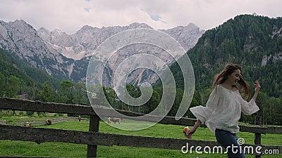 A jovem está pulando e chorando no campo perto dos Alpes e da fazenda filme