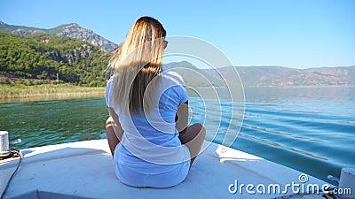 Jovem loiro sentado em arco de barco e flutuando pela superfície calma do lago grande Menina irreconhecível gostando video estoque