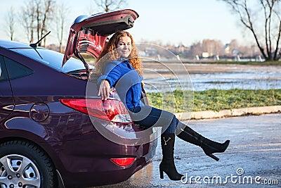 Tronco da bagagem do veículo com mulher de assento para dentro