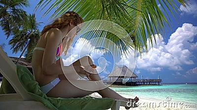 A jovem mulher com pés bonitos usa a proteção solar na praia tropical filme