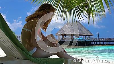 A jovem mulher com pés bonitos usa a proteção solar na praia tropical Movimento lento video estoque