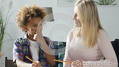 A jovem mulher e o garoto africano estão sentados na mesa e fazendo o dever de casa da escola juntos vídeos de arquivo