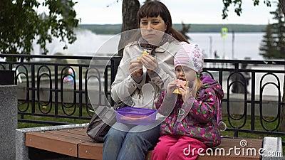 Jovem mulher e sua filha pequena que comem sanduíches no outono do parque vídeos de arquivo