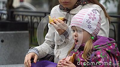 A jovem mulher e sua filha pequena que comem sanduíches no parque refrigeram o dia filme