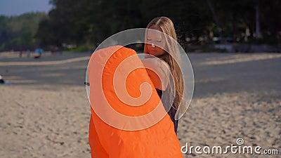 Jovem mulher em uma praia tropical para inflar um sofá inflável Conceito das f?rias de ver?o filme