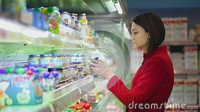 A jovem mulher escolhe os bens em uma mostra filme