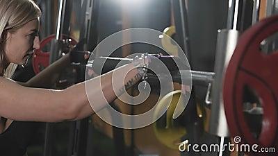 A jovem mulher prepara-se para levantar o barbell pesado A menina executa exercícios da força video estoque