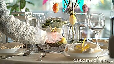 Jovem mulher que ajusta a tabela festiva de easter com a decoração do coelho e dos ovos filme