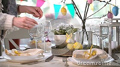 Jovem mulher que ajusta a tabela festiva de easter com a decoração do coelho e dos ovos video estoque